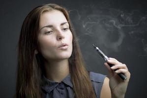 femme élégante, fumer une cigarette électronique avec de la fumée photo