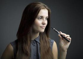 élégante, belle femme fumant une e-cigarette photo