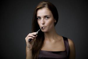 élégante belle femme tenant une e-cigarette photo