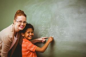 enseignant, aider, garçon, écrire, tableau noir, dans, classe