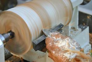 charpentier poignée pièce en bois sur le tour avec un burin