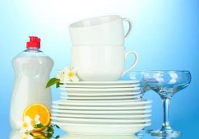 assiettes et tasses vides propres avec du liquide vaisselle et des éponges photo
