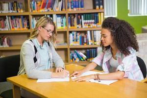 étudiant obtient l'aide d'un tuteur dans la bibliothèque photo