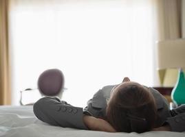 femme d'affaires portant sur le lit dans la chambre d'hôtel. vue arrière photo
