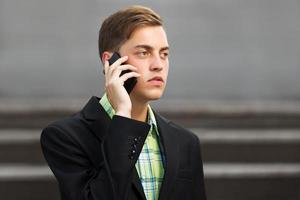 jeune homme appelant sur le téléphone mobile en plein air photo