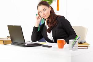 jeune et jolie femme d'affaires dans son bureau de travail photo