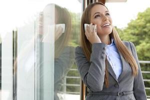 heureux, femme affaires, répondre, téléphone portable, par, porte verre photo