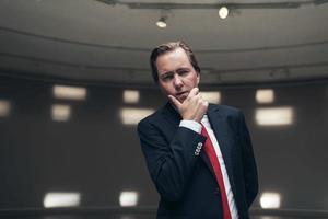entrepreneur concerné avec cravate rouge debout dans une pièce vide. photo
