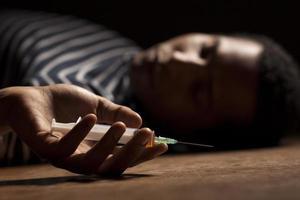 homme africain, coucher plancher, à, seringue, dans main photo