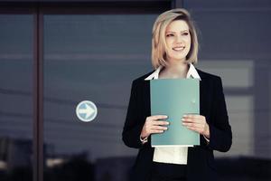 femme d'affaires heureux avec un dossier à l'immeuble de bureaux photo