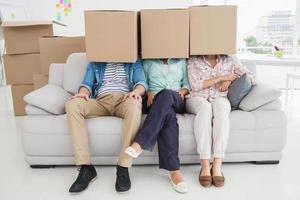 collègues assis sur un canapé couvrant avec une boîte en carton photo
