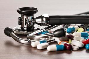 stethoskop und medikamente liegen auf dem schreibtisch photo