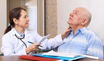 docteur mature touchant le cou de l'homme photo