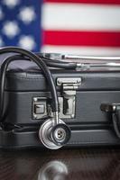 Porte-documents et stéthoscope reposant sur une table avec le drapeau américain soit photo