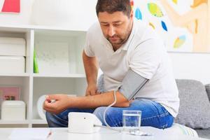 homme mesurant sa tension artérielle, attendant les résultats. photo