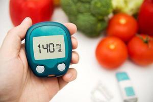main tenant le compteur. diabète faisant un test de glycémie. photo
