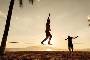 équilibre des adolescents sur la silhouette de la slackline photo