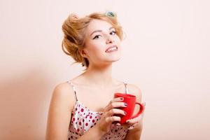 femme au foyer avec une tasse rouge de boisson chaude photo