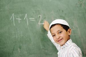 Enfant musulman arabe écrit sur le tableau noir en classe, mathématiques