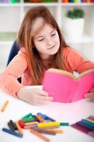 mignonne petite fille rousse lisant un livre photo