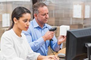 Gestionnaire de numérisation de la boîte pendant que son collègue tape sur un ordinateur portable photo