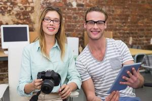 collègues occasionnels avec appareil photo numérique et tablette au bureau