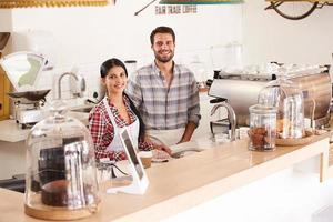 heureux jeune personnel de café, souriant à la caméra photo