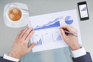 main d'homme d'affaires avec un stylo sur le diagramme graphique photo
