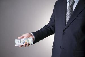 homme d'affaires avec de l'argent en studio. concept de corruption. billets de cent dollars photo