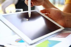 homme d'affaires analyse les statistiques financières affichées sur l'écran de la tablette photo