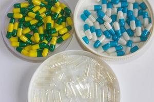 bleu blanc vert jaune et transparent capsule médicament isolé photo
