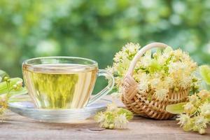 Thé au tilleul sain et panier en osier avec des fleurs de tilleul photo