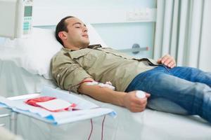 patient transfusé allongé sur un lit photo