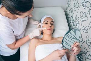 femme médecin montrant au patient les zones du visage pour une photo