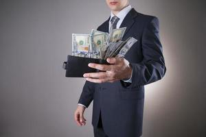 homme d'affaires avec de l'argent en studio sur fond gris photo