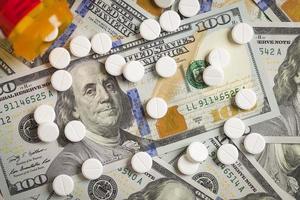 pilules de médecine éparpillées sur un bi de cent dollars nouvellement conçu photo