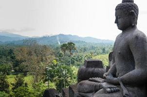 Bouddha assis méditant dans la pierre au-dessus de la jungle à borobudur photo