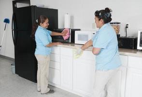 deux femmes de ménage nettoyant une salle de pause d'entreprise photo