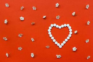forme de coeur en pilules blanches avec motif de fleurs blanches
