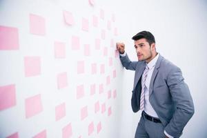 bel homme d'affaires à la recherche sur le mur avec des autocollants photo