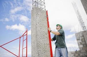 entrepreneur en bâtiment vérifiant les travaux de coffrage en béton sur le site photo