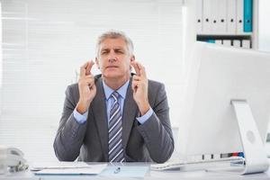 souhaitant homme d'affaires croisant ses doigts