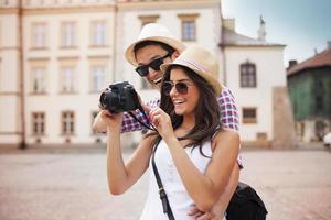 jeune couple regarde des photos sur l'appareil photo