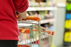 dame poussant un panier dans le supermarché. photo
