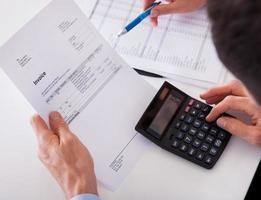 homme vérifiant une facture sur une calculatrice
