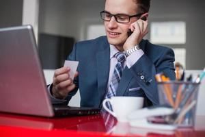 jeune homme d'affaires heureux détenant un téléphone mobile et une carte de visite blanche. photo