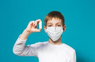 masque de protection garçon tenant des pilules
