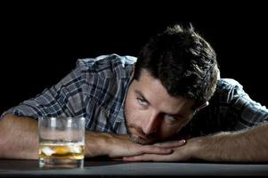 Homme alcoolique ivre avec verre de whisky dans le concept d'alcoolisme photo