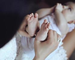 mère posant avec son bébé, tenant ses pieds dans les mains