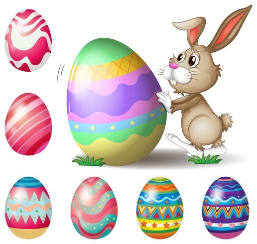 Un lapin poussant un gros oeuf de Pâques vecteur